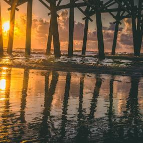 Sunrise through the pier by Travis Wessel - Landscapes Travel ( pier, reflection, beach, ocean., sun, water )