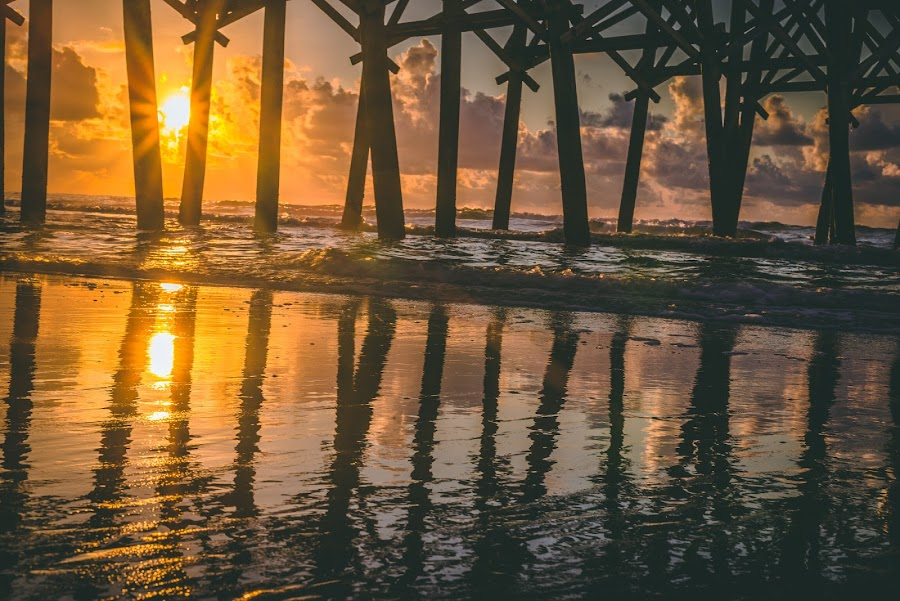 Sunrise through the pier by Travis Wessel - Landscapes Travel ( pier, reflection, beach, ocean., sun, water )