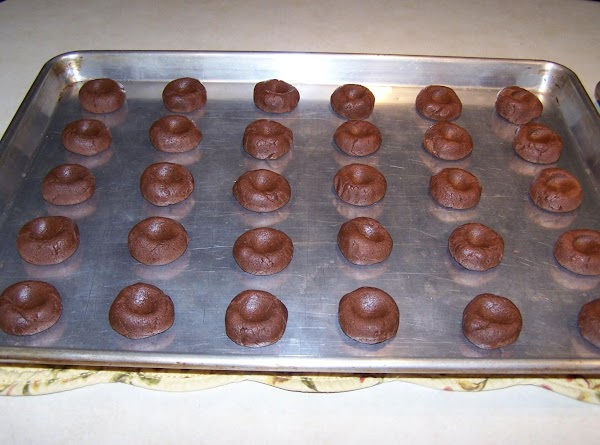 Roll dough into 1 inch balls and place on ungreased cookie sheets. Press down...
