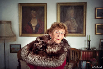 Photo: Hedvig Rossbach Wist, Age 86  Wrapped in her century old fox stole and surrounded by precious heirlooms, she looks on while canvas portraits of her ancestors line the walls. Nestled in the town of Kristiansund on the Norwegian coast, antiques fill her flat.