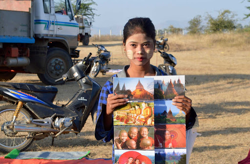 """selling-local-art - Great example of the use of """"thanaka,"""" the traditional sun protection skin treatment on this beautiful woman selling postcards along the road. Brought some home for myself."""