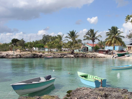 Cuba-Small-Boats-and-Stone-Beach-with-Palm-Trees.jpg - Experience the authentic Cuba on your cruise.