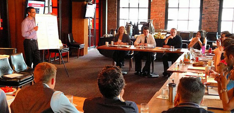 Leaders sitting around a U-shape conference table being taught by a facilitator.