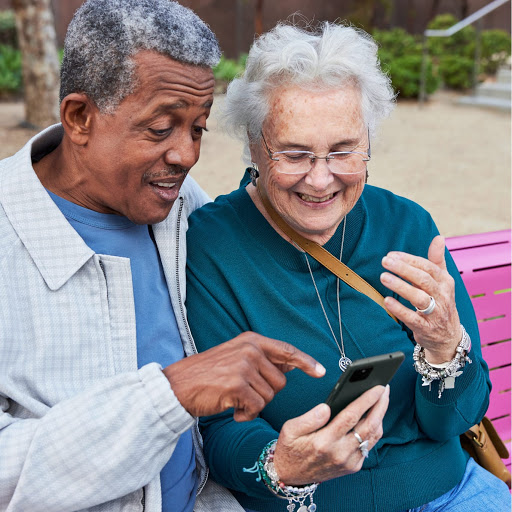 An older couple sits on a bench smiling at a Pixel 5a with 5G as they talk to family members with Duo.