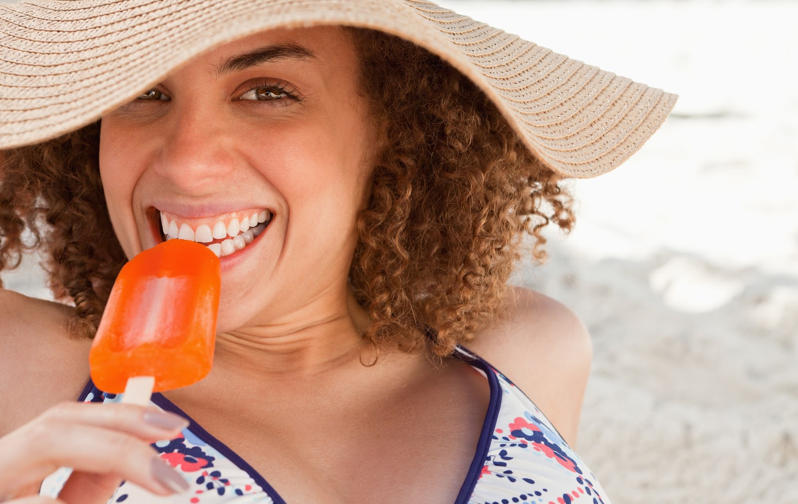 smiling woman enjoying a popsicle while wearing a hat