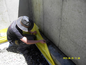 Photo: ... after cleaning the footing we unfold the Stego air/vapor/radon retarder & prepare to seal the slab ...