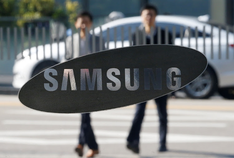 Employees walk past a Samsung sign in Seoul, South Korea. Picture: REUTERS/Kim Hong-Ji