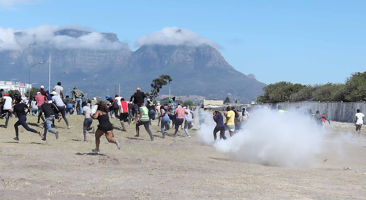 Protesting students at the Western Cape College of Nursing in Athlone, Cape Town, flee as police open fire with stun grenades and rubber bullets.