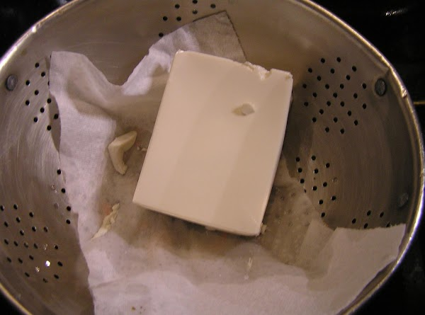 Pre-heat oven to 375.Put package of tofu in a strainer lined with paper towels...