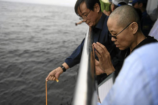 Sorrowful  times:  This municipal   handout photo provided by the Shenyang Municipal Information Office shows late Nobel laureate Liu Xiaobo's wife Liu Xia praying as  Liu's ashes are buried in the sea off   Dalian, Liaoning on SaturdayJuly 15, 2017. Picture: RUETERS