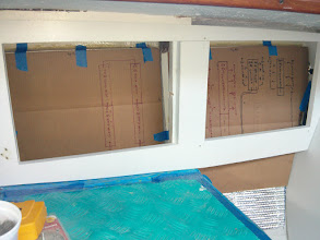 Photo: test fitting electrical panel templates behind new panel frames at nav station.