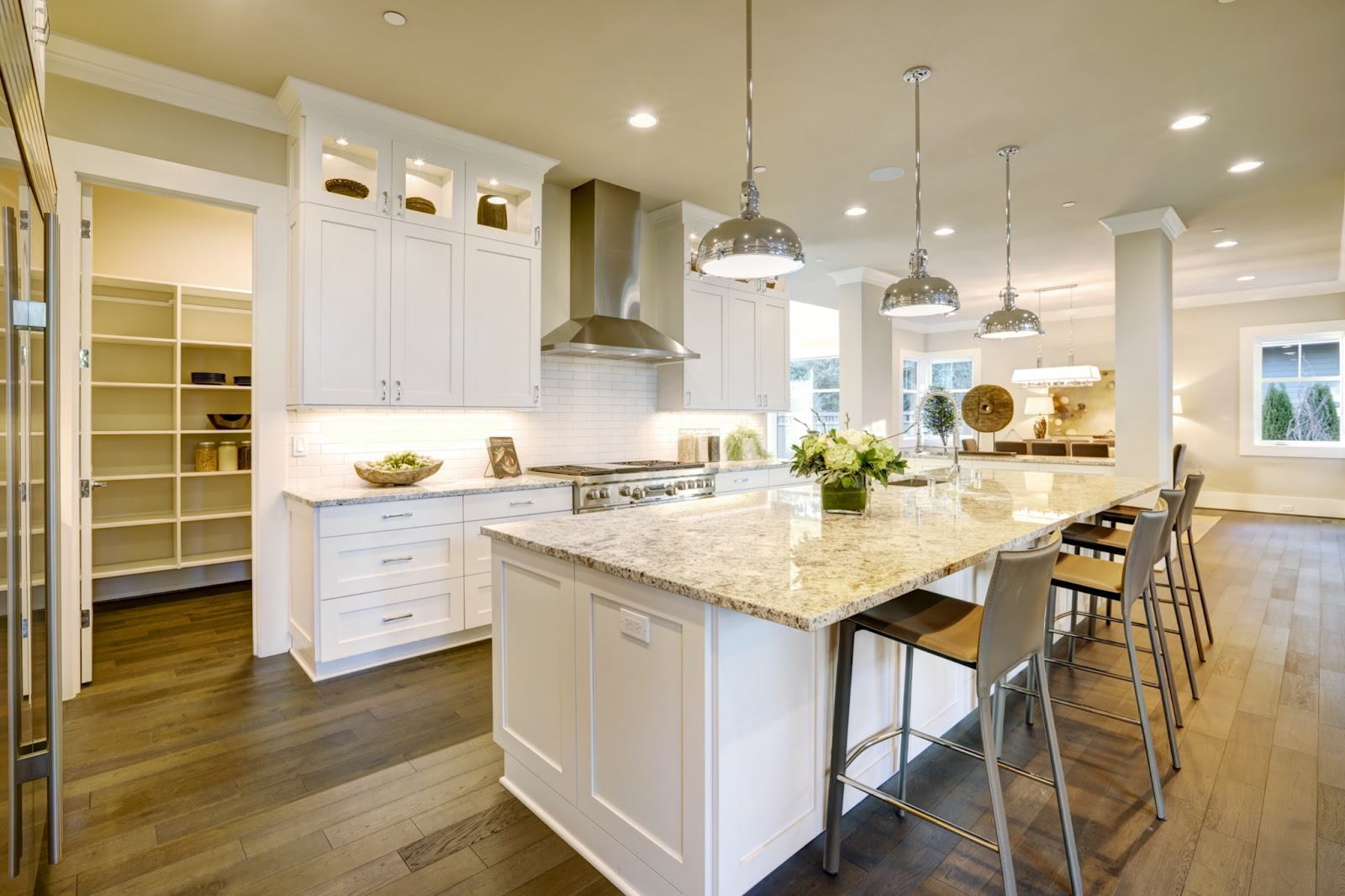 Transitional white kitchen featuring a walk-in pantry behind the stove wall. Kitchen features white shaker cabinets and quartz countertops, large stainless pendants and appliances and wide plank wood floors.