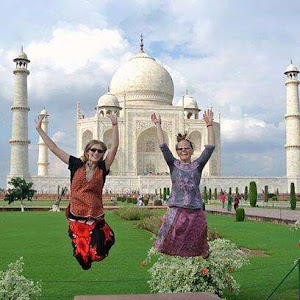 Women Travelers exploring the Taj Mahal in India and making a jumping photo together