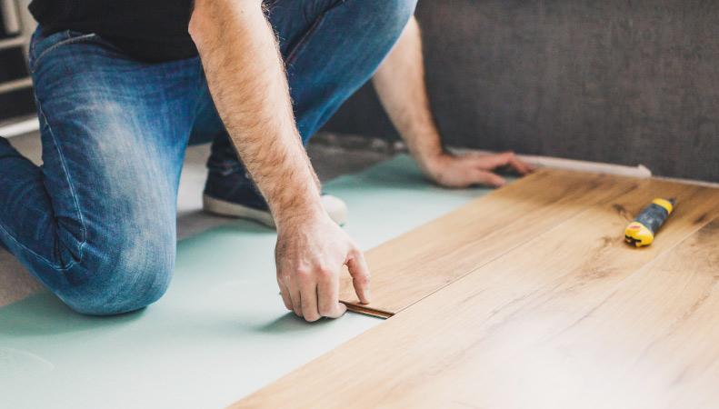 A man putting new flooring down
