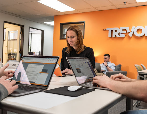 Three people working on laptops at the Trevor Project office.