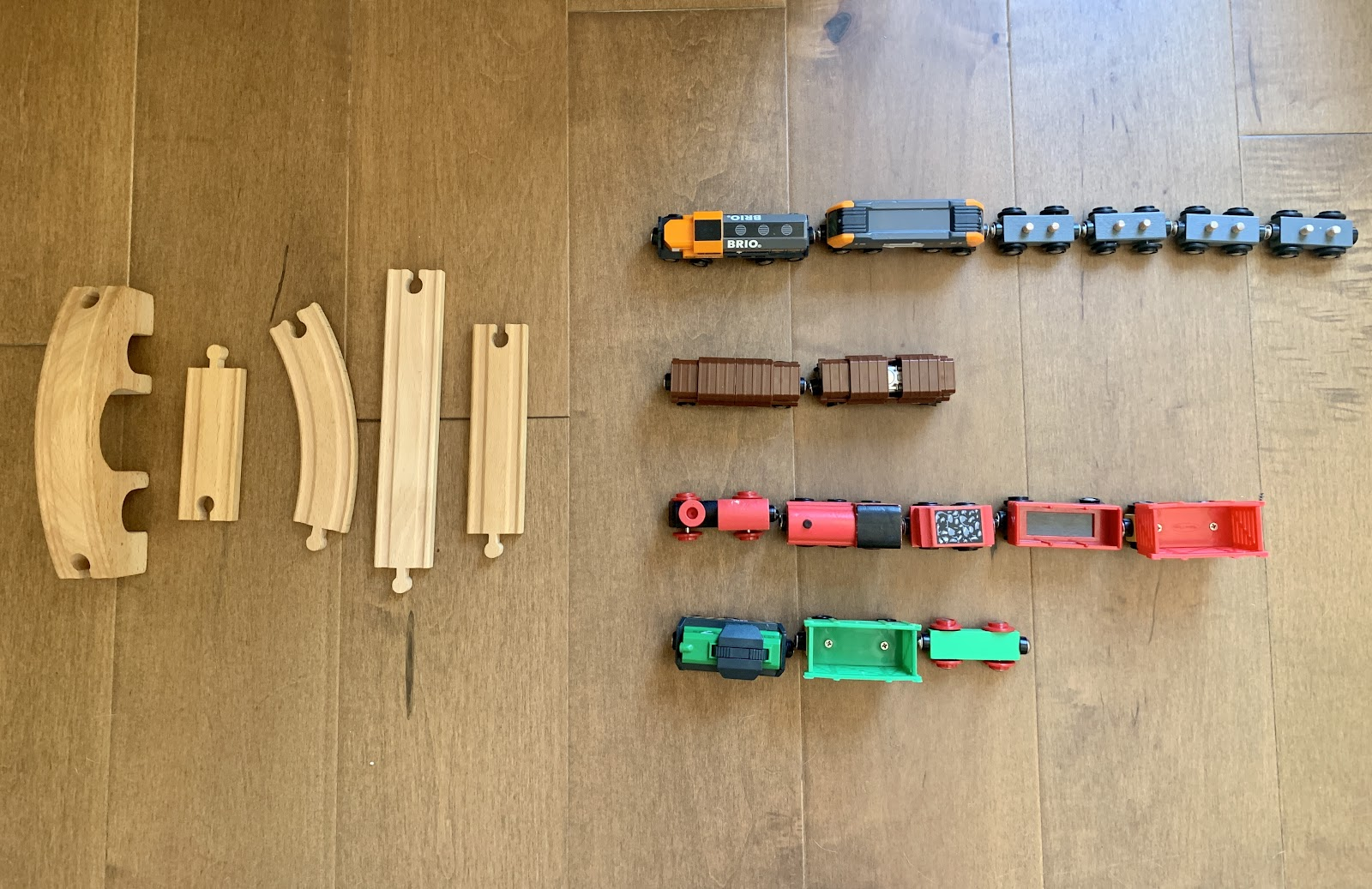 5 train track pieces. 3 are straight and 2 have curves. 4 rows of train cars. One row has 6 gray train cars. Then a row of 2 brown train cars. Next a row of 5 red train cars. And a row of 3 green train cars.