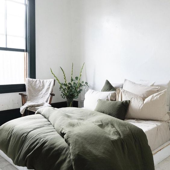 Fall bedroom decor shows a bedroom with a mostly white setting. White walls and natural colored bedding with a dark green plush comforter and green throw pillows.