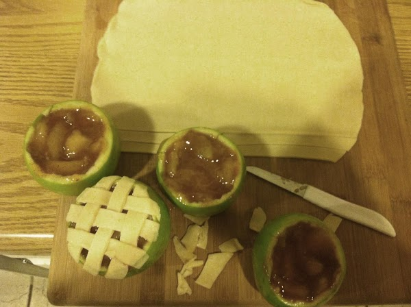 lay strips of dough on top of the apple. then take a new strip...