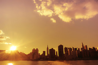"""Photo: """"Sun-kissed...""""  Late summer and early autumn sunsets in New York City are intensely beautiful. The city seems to cling to every bit of sunlight through a haze that sleepily hangs low over the urban waterfront. This was taken near the end of a four hour long ferry ride back and forth around the East River in the late summer. There were barely any people on the ferry that day and I spent entire rides just taking note of the sun's descent in the sky.  When this moment occurred, it was so brief and fleeting and yet so dramatic in its intensity as the sun dipped towards the midtown skyline grazing the skyscrapers that I barely even knew if I captured it properly since the waves were kicking up in the river and the boat was swaying up and down over the waves. By then, I had gotten my 'sea legs' and knew the exact way to stand and counter the movement with my camera in my hands.  And the sun-kissed skyline drifted away from view and descended into the twilight of evening.    New York Photography: The Empire State Building, Chrysler Building and skyscrapers of midtown Manhattan at sunset.    Taken with the Sony A77.    You can view this post along with all relevant links over at my photography blog here if you wish:  http://nythroughthelens.com/post/43566602327/the-new-york-city-skyline-in-midtown-manhattan-at  -  Tags: #photography  #nyc  #newyorkcity  #nycphotography  #newyorkcityphotography  #sunset  #city  #cityscape  #cityphotography  #urban  #urbanphotography  #urbanlandscape  #nycsunset  #skyscrapers"""