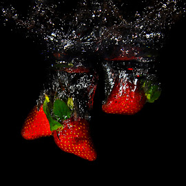 Fallen Strawberries by Chandra Irahadi - Food & Drink Fruits & Vegetables ( water, splash, fruits, food photography, splash water photography, splash water, strawberry, black background, red, splashing, food, strawberries, fruits and vegetables )