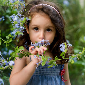 Blossom by Elias Spiliotis - Babies & Children Child Portraits ( little girl, blue, smelling, green, candit, flowers, garden, portrait, blossoms, eyes,  )