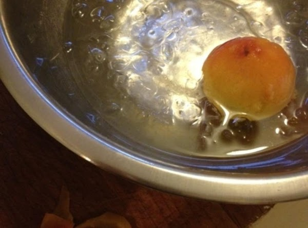 Remove from stove and put one peach at time into a bowl full of...