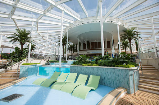 Relax, unwind and enjoy a dip in the pool or whirlpool as you admire 360-degree views in the Solarium aboard Anthem of the Seas.