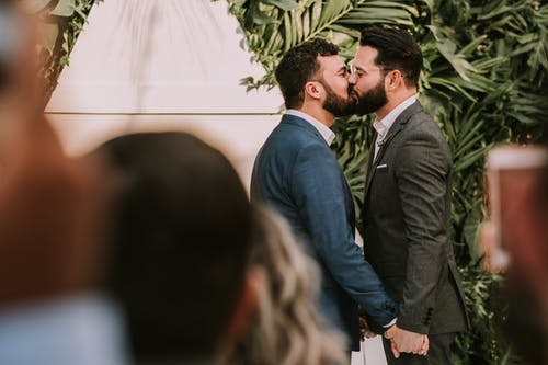 Image of couple kissing at wedding ceremony.