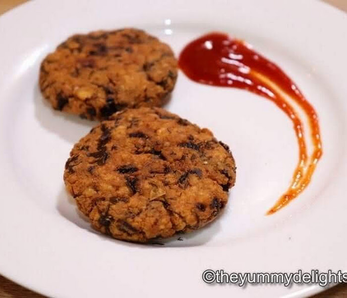 close up of crispy chana dal vada served in a plate with tomato sauce