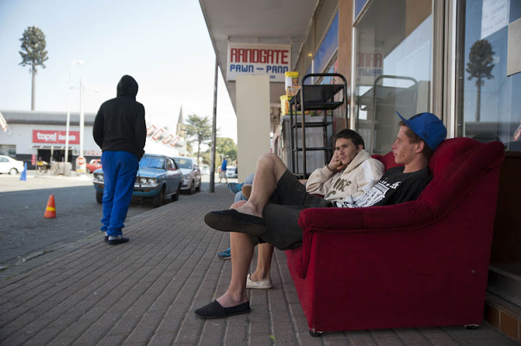 Two unemployed youths lounge around on a couch outside one of many pawn shops in Randfontein.