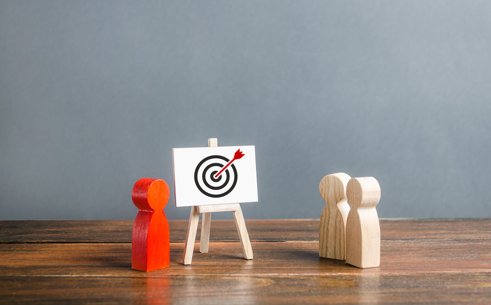 Mini red wooden figurine standing next to mini board with a target painted on it where the arrow hits the bullseye. Look like the red figurine is explaining the STP marketing model to two other brown mini figurines