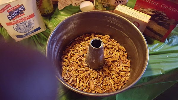 Place pecans in greased tube pan and set aside.