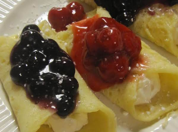 Crepes Made With Thin Pancake Batter From A Mix Filled With A Simple Cream Cheese Mixture Then Topped With Canned Fruit Pie Filling!