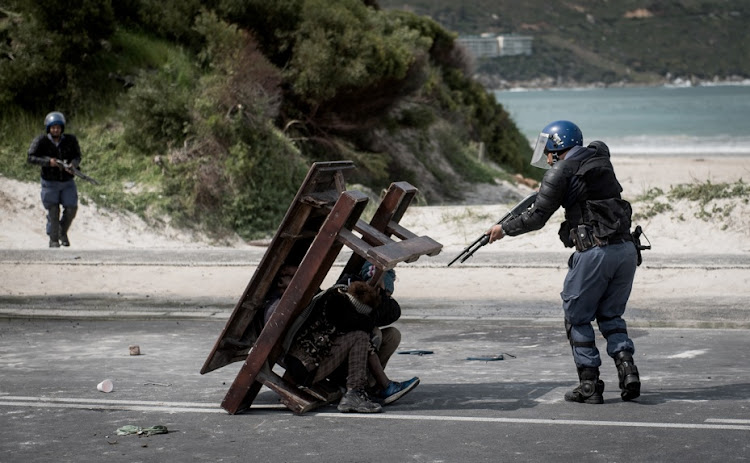 Police move in to clear barricade set up by Hangberg protesters. A young boy is shot in the face by a rubber bullet.