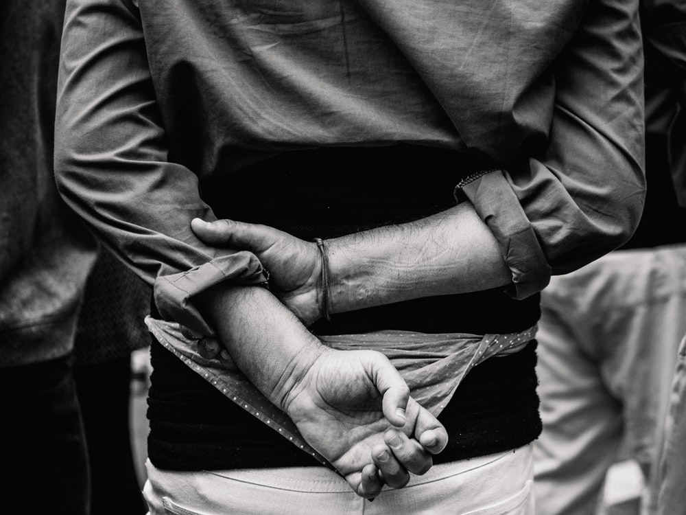 grayscale photo of person with hands on back