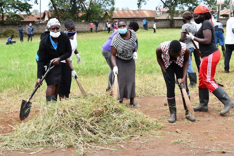 Youth engaging in cleaning exercise at Shaurimoyo Primary School in Kisumu during the launch of the second phase of Kazi Mtaani project on July 14