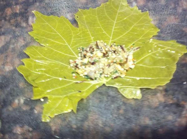 Take grape leaf, lay shiny side down(back of leaf up), cut off stem. Place...