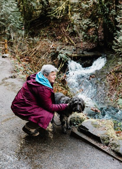 A woman in a purple raincoat pets a large grey dog near a small stream as a way to support her wellbeing.
