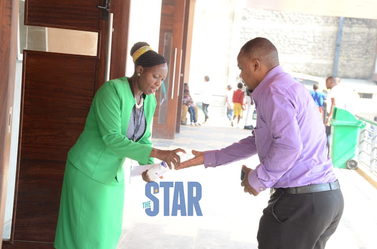 An usher applies a hand sanitiser to the worshippers before the service at Deliverance Church Umoja, Nairobi on March 15, 2020./DOUGLAS OKIDDY