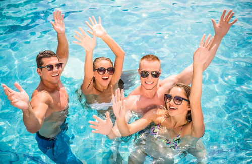 This picture is of a group of sun-glass wearing young adults, hands in the air, in a swimming pool