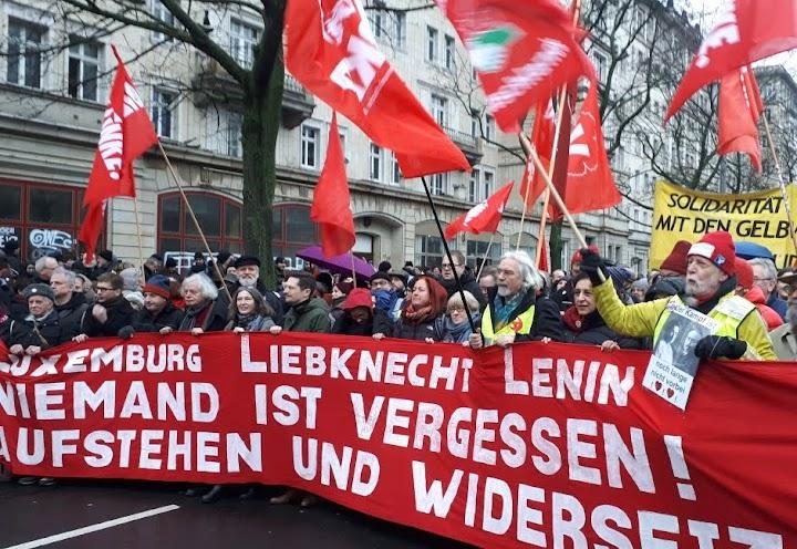 Demonstrant:innen mit roten Fahnen von DKP und PDL, Transparent: «Luxemburg Liebknecht Lenin. Niemand ist vergessen! Aufstehen und widersetzten».
