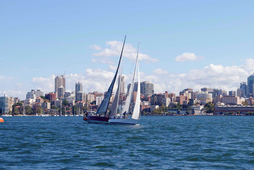 Sydney-skyline-and-sailboat - A sailboat wafts in Sydney Harbour against the city skyline.