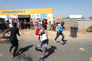 Soweto residents loot a shop owned by a foreigner.