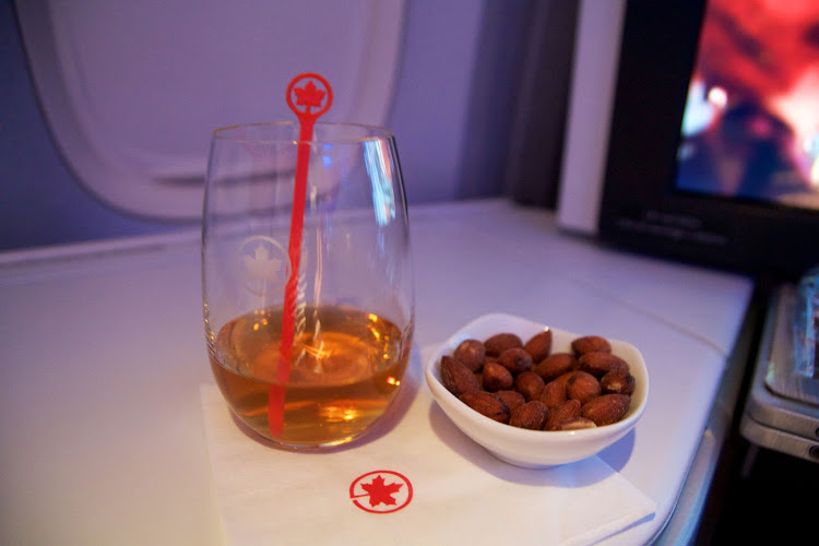 A glass of whisky and some warm nuts on a folding table inside a Boeing 777-300ER.