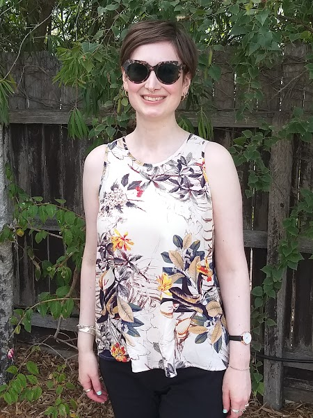 Siobhan stands in front of a garden fence. She wears a tank top with narrowed shoulders and slight scoop neck, in a beige printed rayon. She wears large tortoiseshell sunglasses and is smiling.