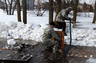 Photo: Spcs. Scott Nielson, left, and Dan Francis, both infantrymen from Company A, 2nd Combined Arms Battalion, 136th Infantry Regiment, adjust a pump to battle a breach in a sandbag wall as the Red River continues to rise in Moorhead, Minn., Friday, March 27, 2009. The Red River continues to rise as a result of rain and snowmelt and is expected to crest at 43 feet, three feet higher than the current flood record. More than 500 Minnesota National Guard Soldiers and Airmen have been called up to state active duty to assist local authorities with traffic control, security as well as other tasks.(U.S. Army photo by Staff Sgt. Jon Soucy)(released)