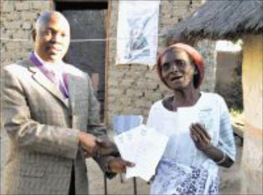 HAPPY ENDING: Home Affairs official Eddie Maphosa hands over a birth certificates and an ID to granny Mokwape Mmola yesterday. Pic: MICHAEL SAKUNEKA. 11/08/2009. © Sowetan.