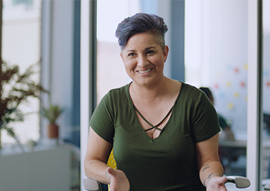 woman smiles while sitting in a chair in an office