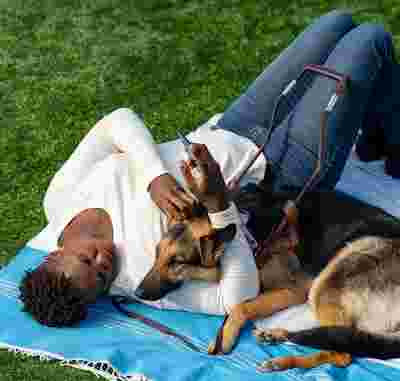 A person lying down with their dog.