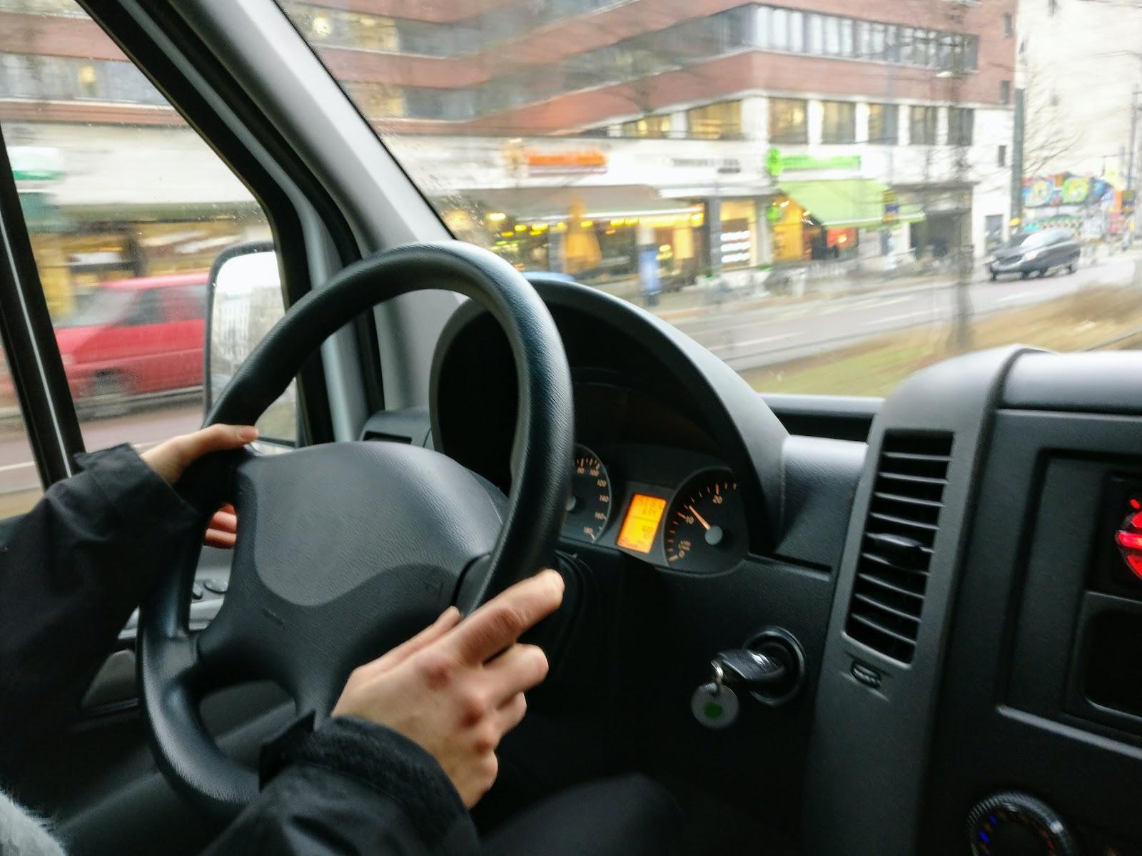 Mãos de motorista no volante do carro.